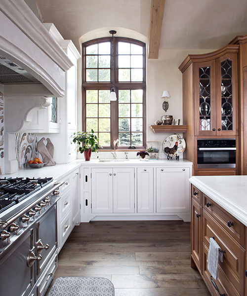 Luxury kitchen remodel designed by William Ohs in Denver featuring custom cabinetry in medium-colored wood and white wood
